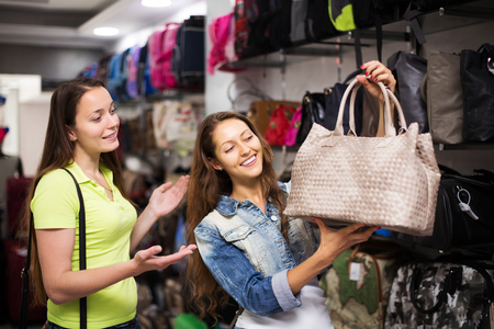 leather bag: Two smiling women choosing leather bag in shop