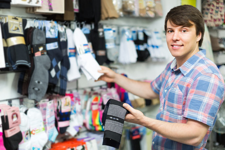 30 s: Happy smiling young man buying socks at store Stock Photo