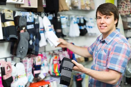 socks: Happy smiling young man buying socks at store Stock Photo