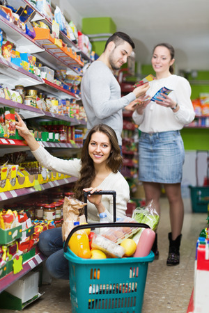 tinned: Smiling adults choosing tinned food at supermarket
