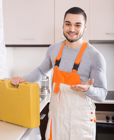 successfully: Smiling plumber successfully working at home of client