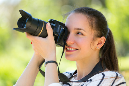 photocamera: Portrait of cheerful smiling girl with photocamera at park Stock Photo