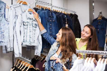 Two young smiling girls buying vest in clothing store