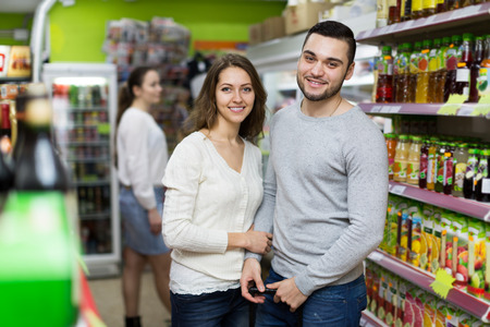 30 to 35: Portrait of young happy customers standing at beverages section of the supermarket