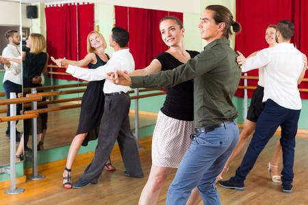 merry dancers: Three smiling couples dancing tango in dancing studio. Selective focus