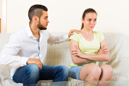 resent: Depressed young couple sitting at the sofa after quarrel. Focus on girl Stock Photo