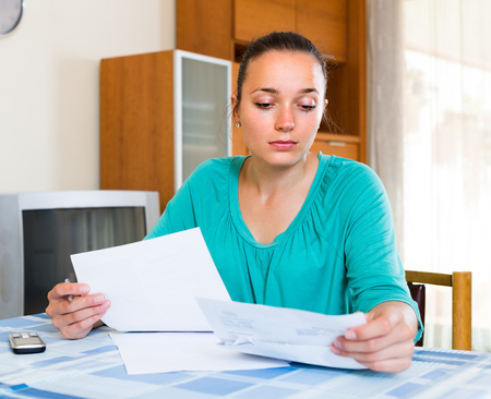 filling out: Sad young woman filling out tax forms while sitting at her desk