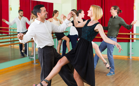 ballroom dancing: Cheerful couples enjoying active dance at studio Stock Photo