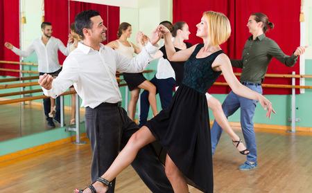 dancing man: Cheerful couples enjoying active dance at studio Stock Photo