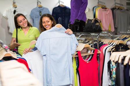 25 35: Smiling young females choosing blouse in clothing store