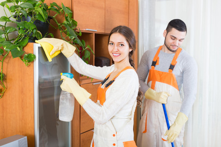 houseman: Cleaning premises team in uniform working at clients home. Focus on girl