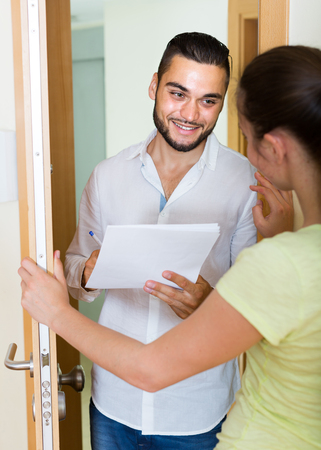 russian man: Smiling russian man and woman standing with papers at the door Stock Photo