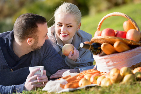 sandwitch: Loving young smiling couple chatting as having picnic in sunny day