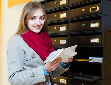 correspondence: La muchacha positiva en el abrigo de control de la correspondencia en el lobby Foto de archivo
