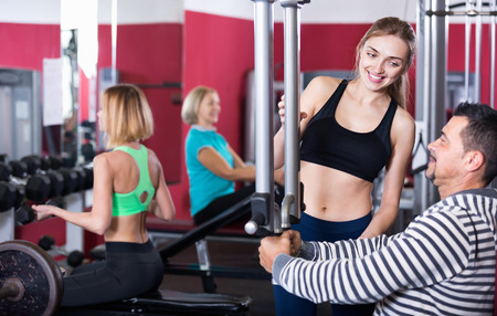 satisfied people: Active positive satisfied people  weightlifting training in modern health club Stock Photo