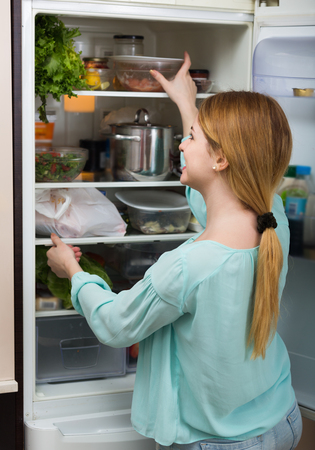 arranging: long-haired russian woman arranging space in fridge at home