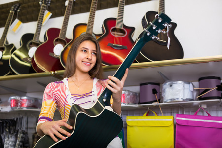 17 20: Excited smiling teenage girl choosing classical guitar in shop Stock Photo