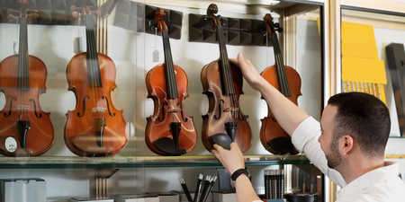 violins: Positive man with beard purchasing traditional violins in store