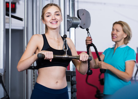 55 60: smiling american females of different age strength training in gym for women