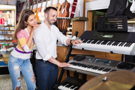 shopgirl: Young smiling cheerful couple choosing synthesizer in music instruments shop