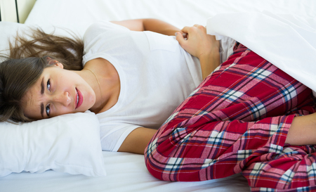 miserable: Miserable young female suffering of colicky pain in bedroom