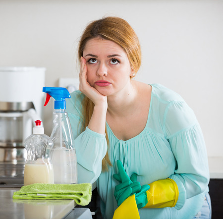unwillingness: Exhausted young housewife taking a break as cleaning in kitchen