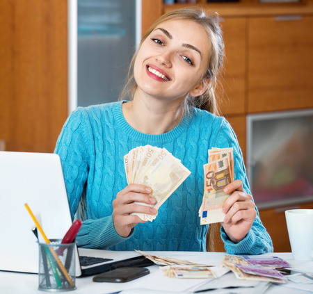 freelancer: Positive young woman earning money at home being freelancer
