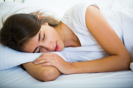 taking nap: Relaxed girl in pyjamas taking nap during siesta indoors
