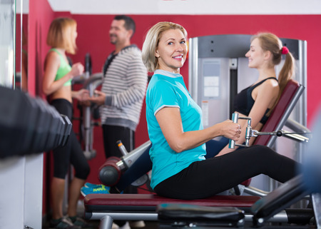powerlifting: Positive smiling women and man doing powerlifting on machines in gym