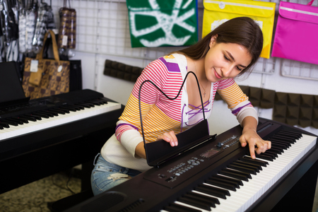 synthesiser: Happy young girl selecting control keyboard for synthesiser in shop Stock Photo