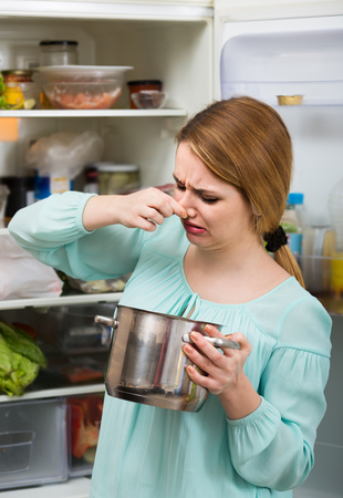 foul: Long-haired american woman noticed foul smell of food from casserole