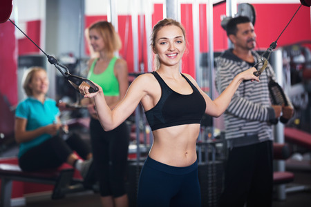 satisfied people: Active smiling satisfied people  weightlifting training in modern health club