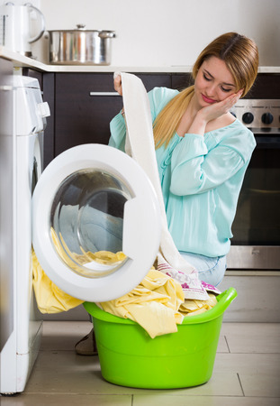 mildewed: Tired woman with musty linen after lame laundry at home Stock Photo