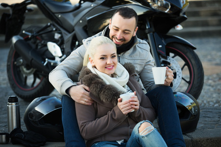 sandwitch: Portrait of couple drinking coffee and chatting near motorcycle