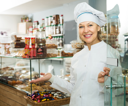 mature female: Happy mature chef with hat meeting customers at door in pastry shop