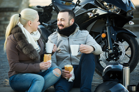 sandwitch: happy couple posing near motor bike with sandwitches and coffee