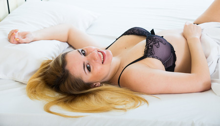 girl boobs: Portrait of young blondie in sexy lingerie at bedroom interior