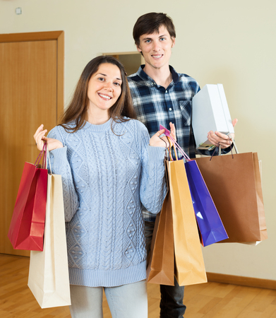 nice guy: Nice guy and girl holding purchases in hands at home