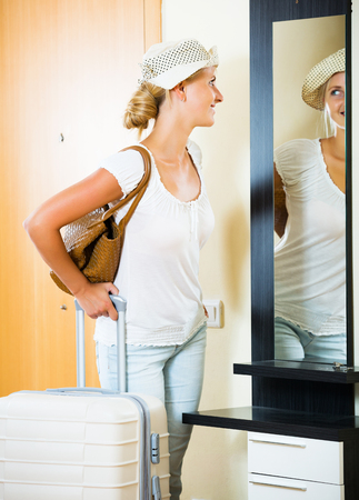 interphone: Blonde young girl standing with luggage near entrance indoors