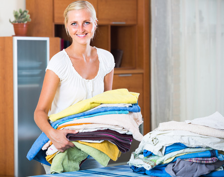 sorting out: Smiling young blonde woman sorting out laundry at home