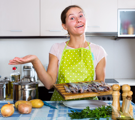 25 35: Positive woman trying new recipe of sprattus in kitchen
