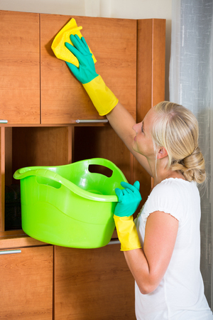 regular people: Young woman in rubber gloves dusting furniture at home and smiling Stock Photo