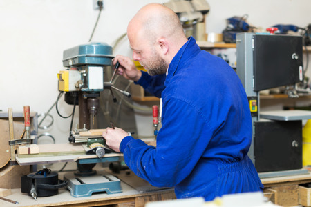 toolroom: ?oncentrated male professional craftsman working with unfinished guitar indoors
