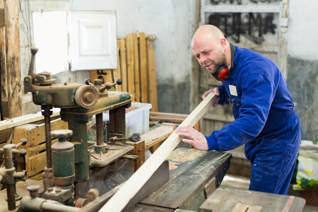 woodworker: Portrait of concentrated adult woodworker on lathe at musical instrument workroom