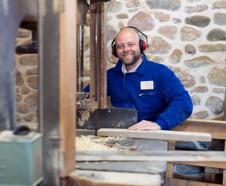 40 45: Portrait of professional carpenter in a blue uniform wearing hearing protection working on a power-saw bench