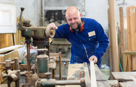 buildup: Skilled woodworker is processing planks of wood on a power-saw in a manufactory Stock Photo