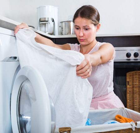 25 35: Upset brunette woman with musty linen after laundry at home Stock Photo