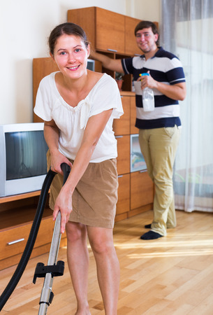 cleanup: Wife with husband doing  regular clean-up in living room