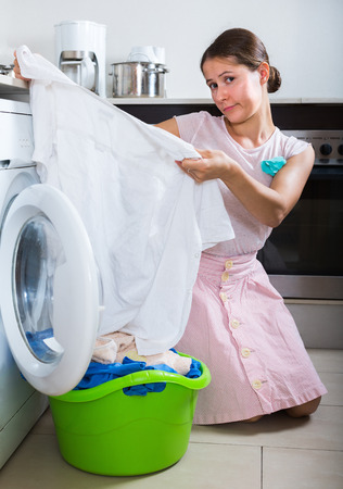 loathsome: Upset young woman with musty linen after laundry at home
