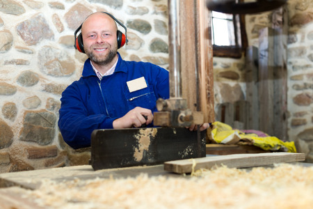 workroom: portrait happy male worker on lathe at  wood workroom